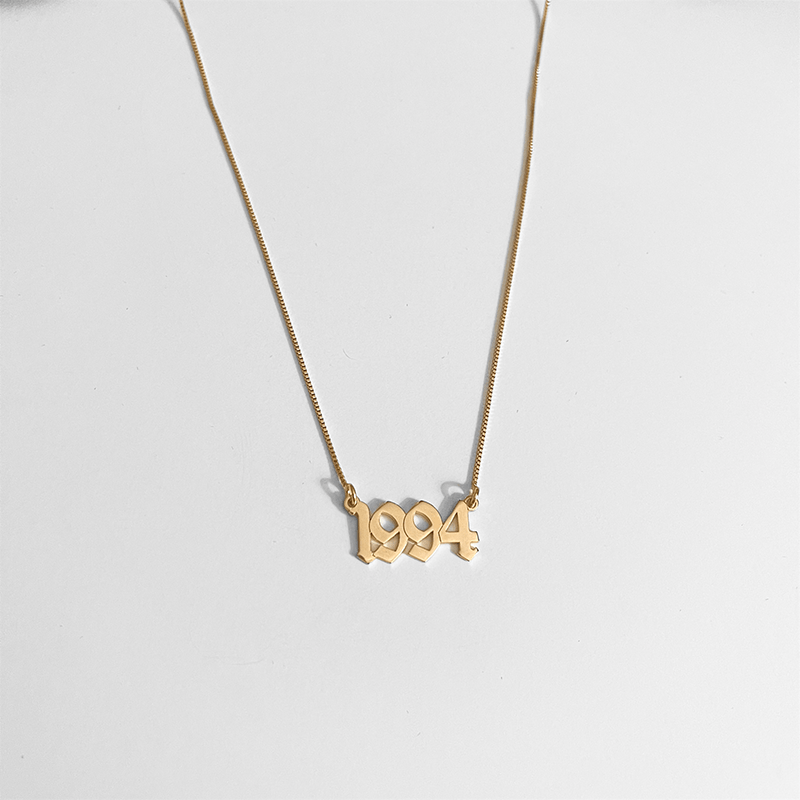 custom necklace in gold on gray background