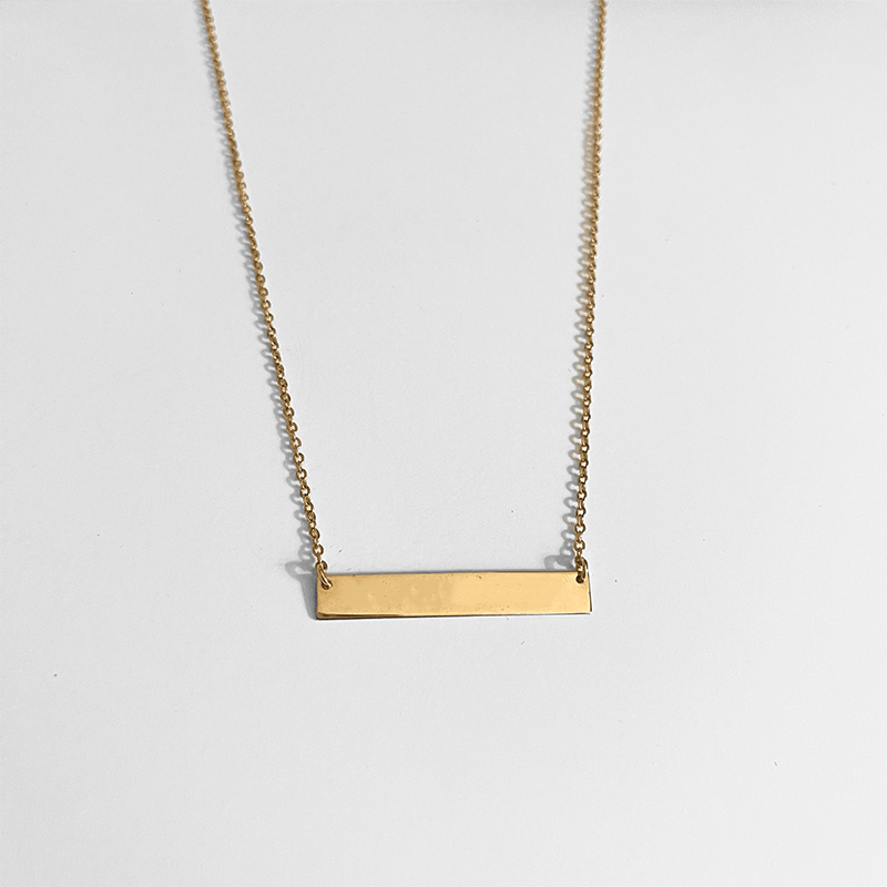 gold bar necklace on gray background
