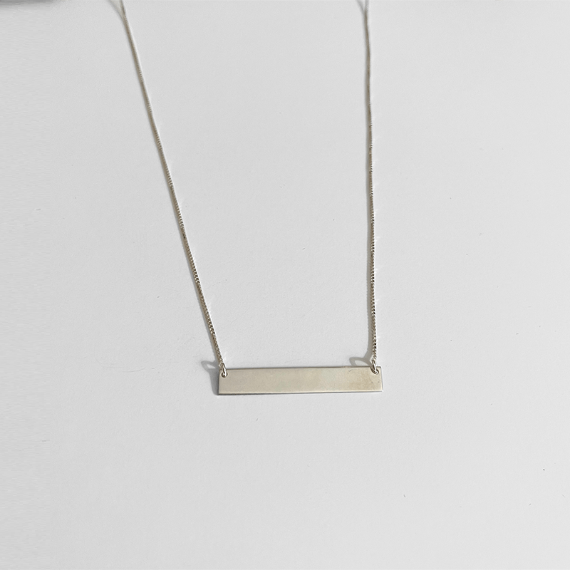 silver bar necklace on gray background