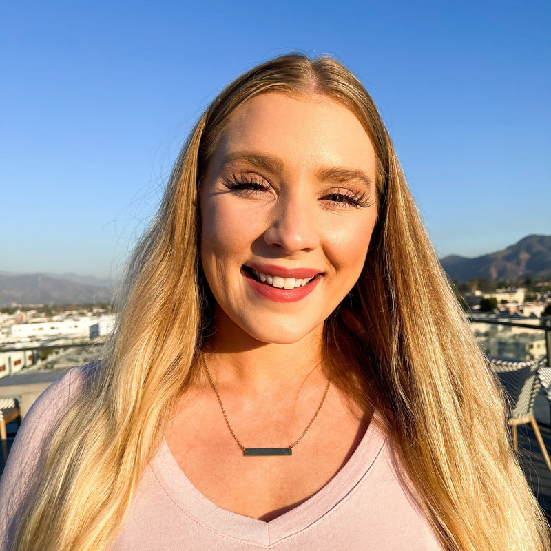 Blonde white woman with blue eyes wearing a gold plated name bar necklace and pink lipstick, smiling and facing the camera with her hair blowing in the wind and a blue sky behind her. She's wearing a pink shirt at golden hour.
