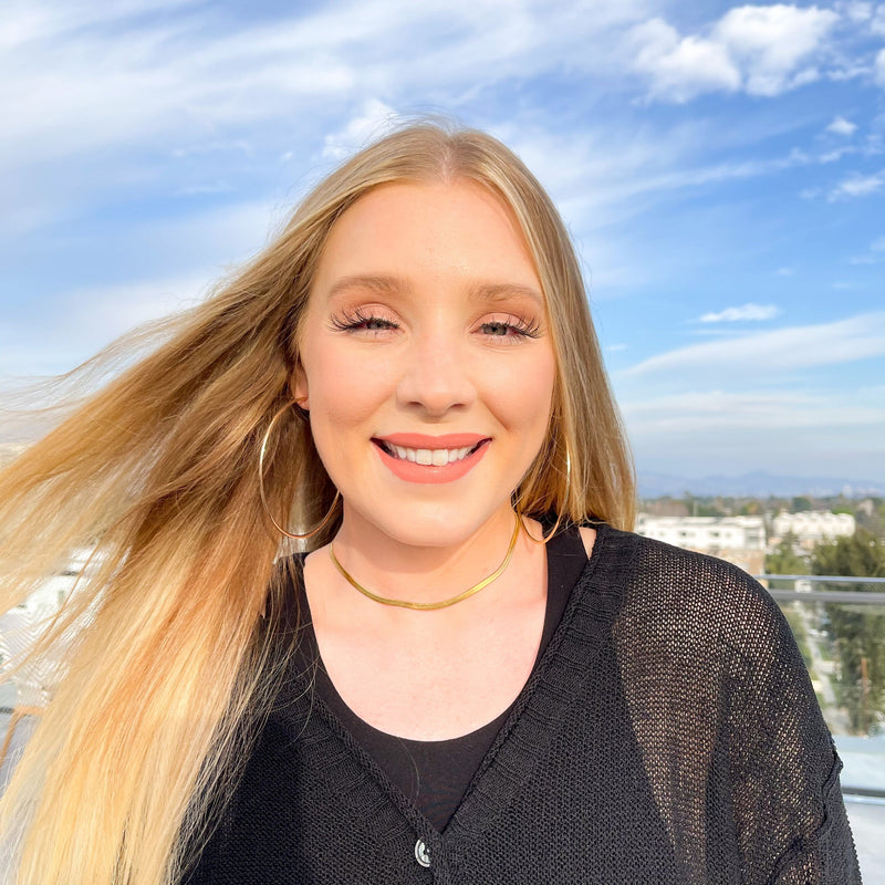 Blonde white woman with blue eyes wearing herringbone gold choker necklace and gold hoop earrings and pink lipstick, smiling and facing the camera with her hair blowing in the wind and a cloudy blue sky behind her. She's wearing a black sweater and black tank top.