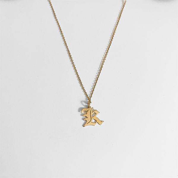 gold initial pendant on gray background