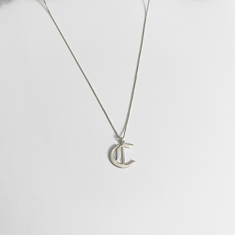 initial necklace silver on gray background