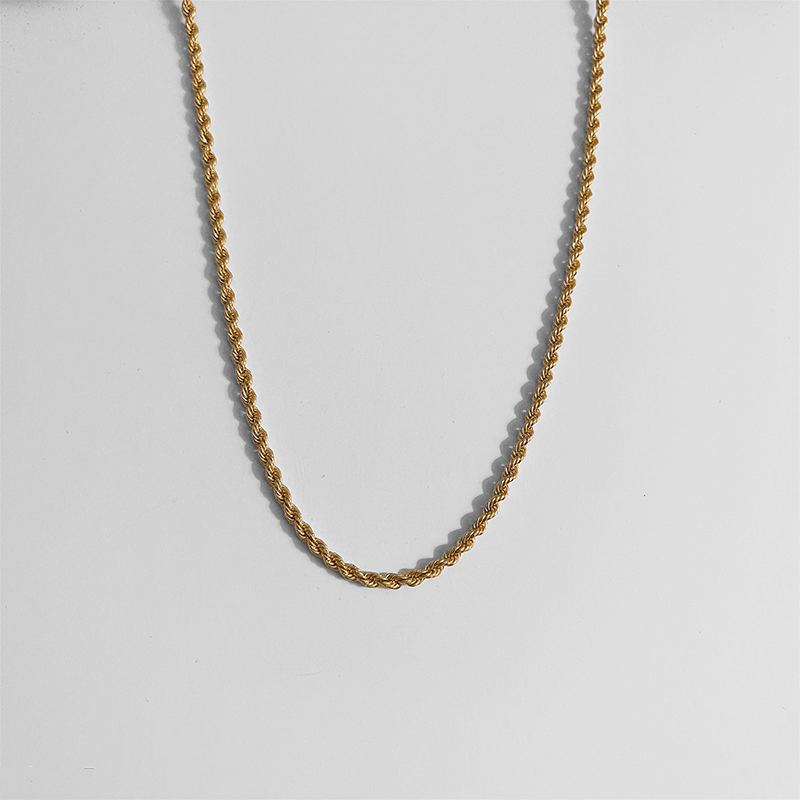 rope necklace in gold on gray background