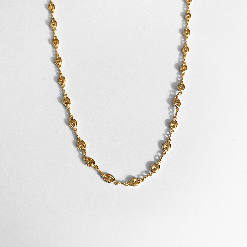 gold necklace on gray background