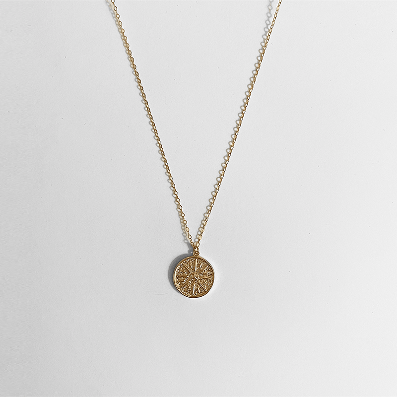 Sun necklace on a gray background with a cable chain