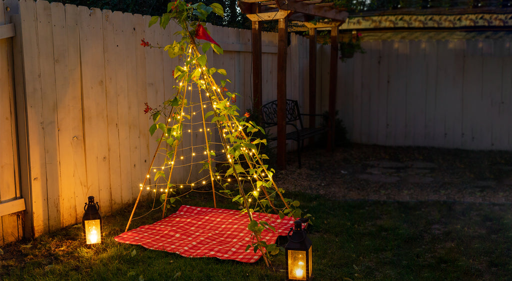 solar string lights and lanterns at dusk on backyard play tent bean teepee