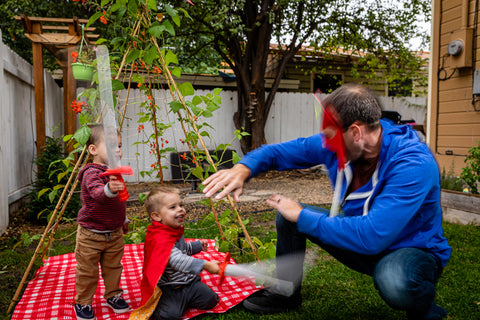 father and sons role playing with sword and cape in backyard play tent