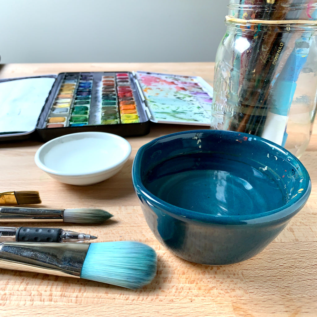 Close up image of 2 bowls of water and some brushes on a wooden table