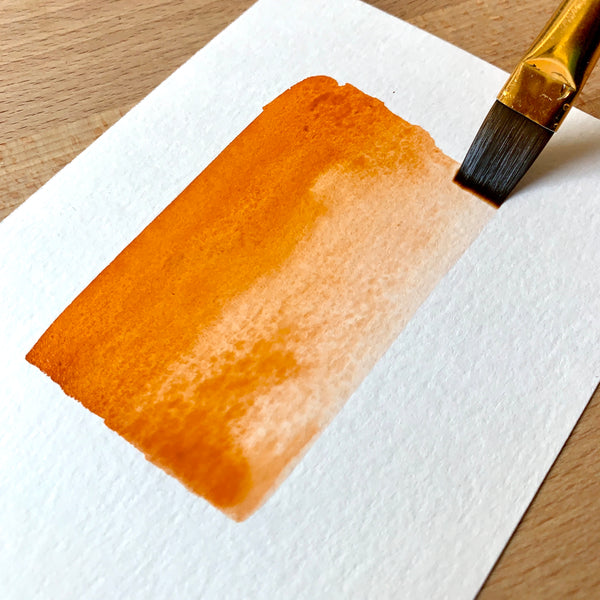 Close up of a paint brush filled with orange paint on paper