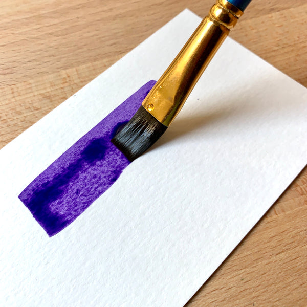 Close up of brush filled with purple paint on paper