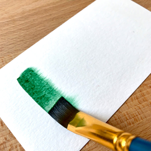 Close up of a paint brush filled with dark green paint on watercolour paper