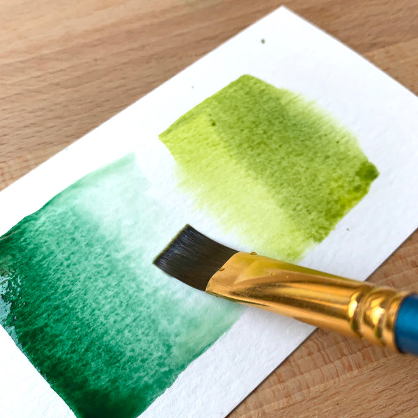 Close up of a paint brush filled with dark and light green paint on watercolour paper