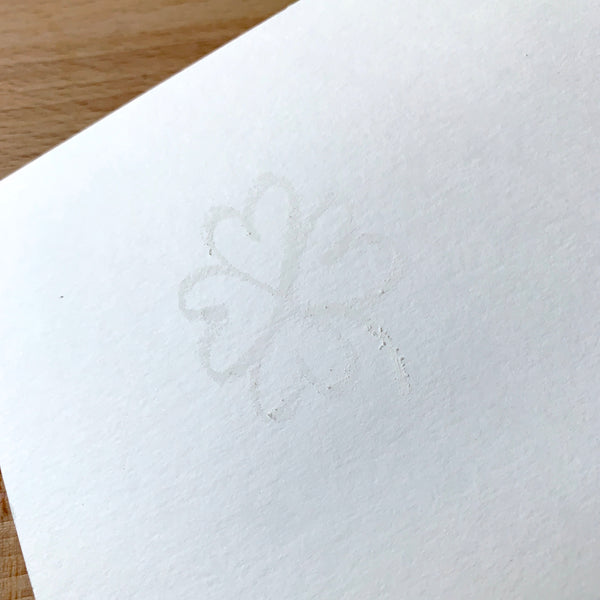 Faint image of a shamrock drawn in white crayon on white watercolour paper