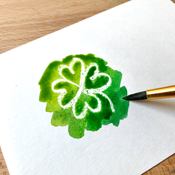 Close up of a white shamrock and some green paint on watercolour paper
