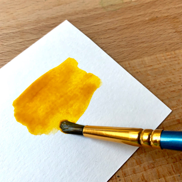Close up of a yellow orange paint being painted via brush on watercolour paper