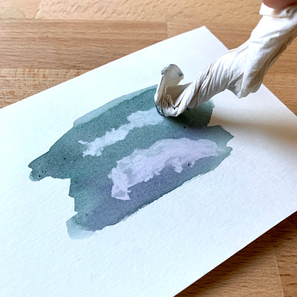 Close up of a piece of watercolour paper and paint, with paper towel dabbing the paint