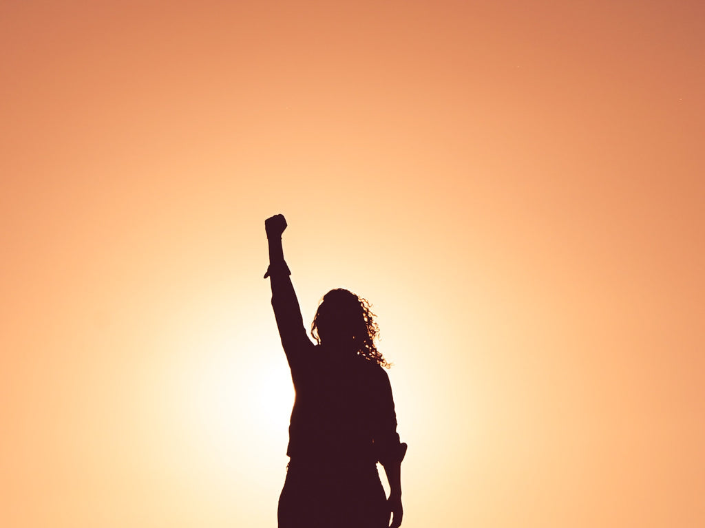 black silhouette of a woman with her hand raised in a fist with an orange background