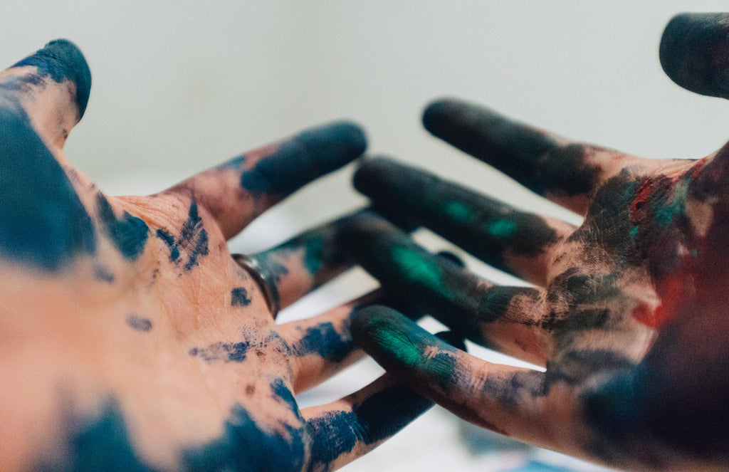 Amauri Mejía photograph, close up of artist's hands with black and coloured paint on the palm and fingers