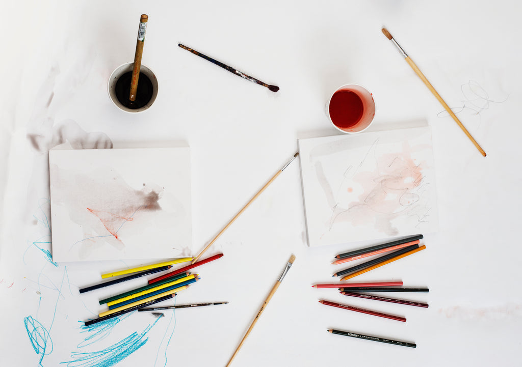 flatlay image of a messy desk with paintbrushes and pens on top of paper