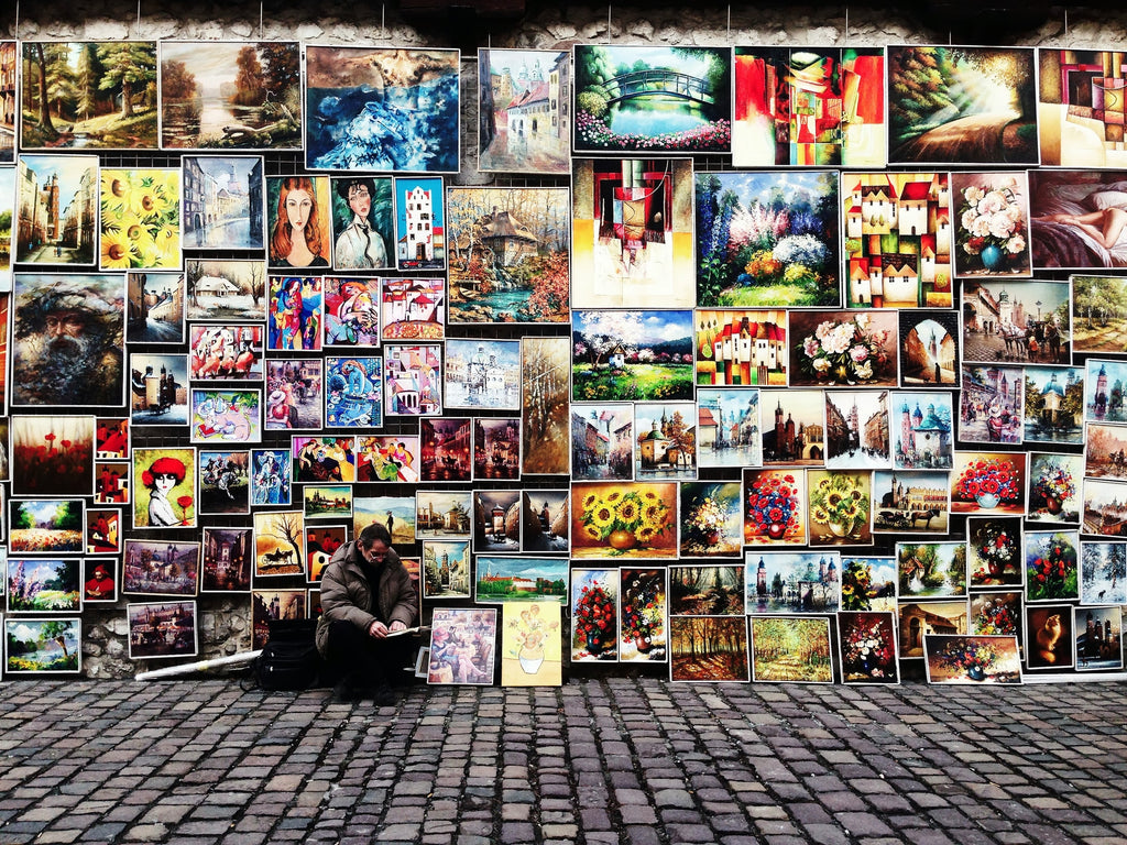 Beata Ratuszniak photograph of an artist on a street trying to sell, with all of his artwork lined up around him