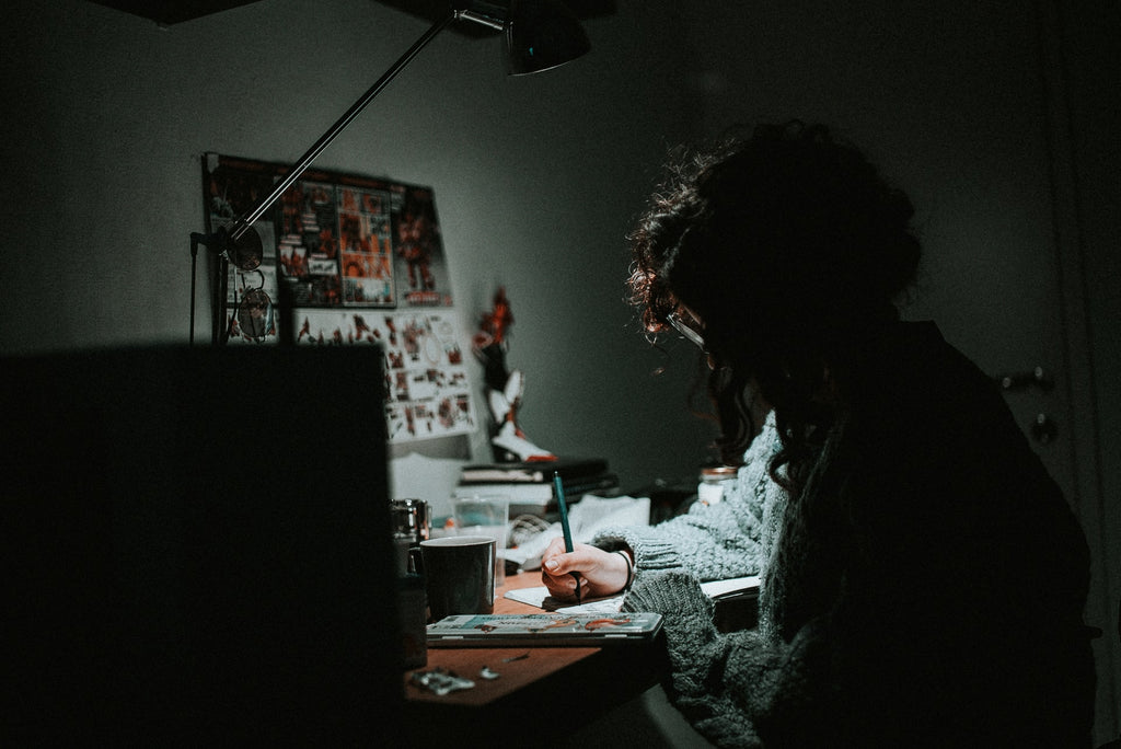 Daniel Chekalov photograph of a black room, a small light, and a female artist painting