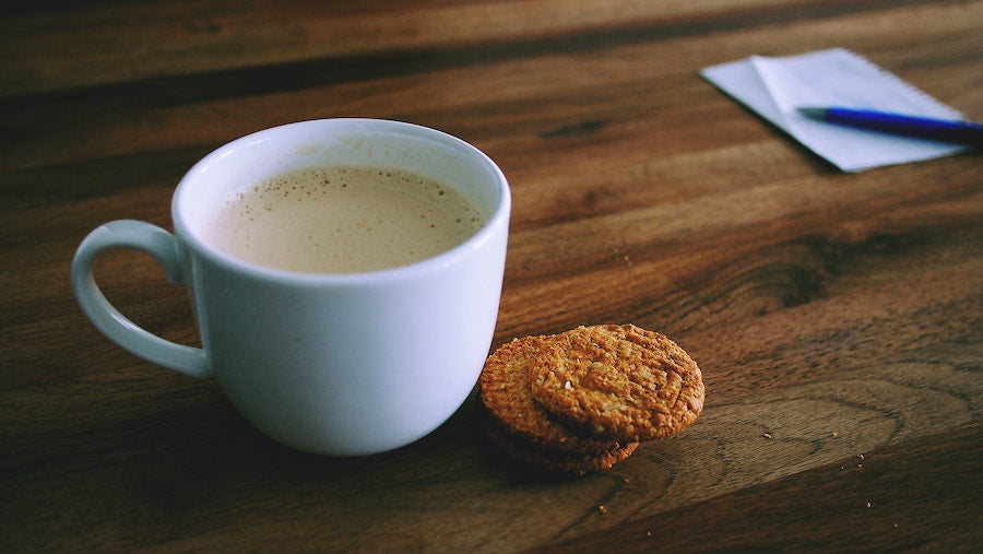 Close up image of a cappuccino and two cookies on a wooden desk
