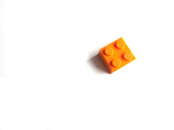 Single square orange megablock piece on the right hand side of a white background