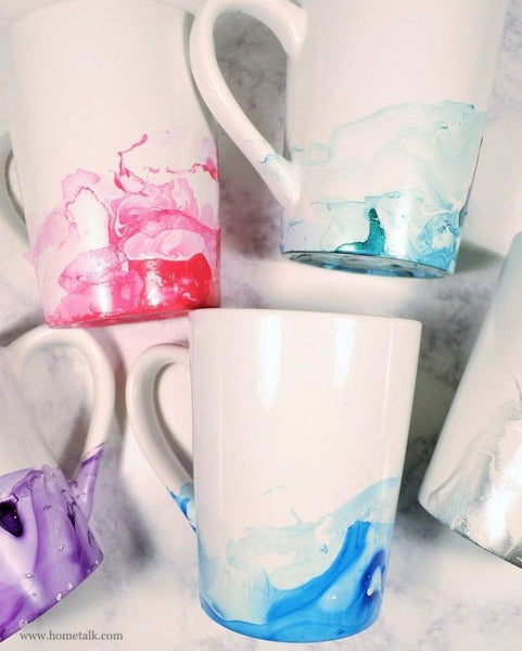Close up image of 5 white mugs with marbled effect on bottoms