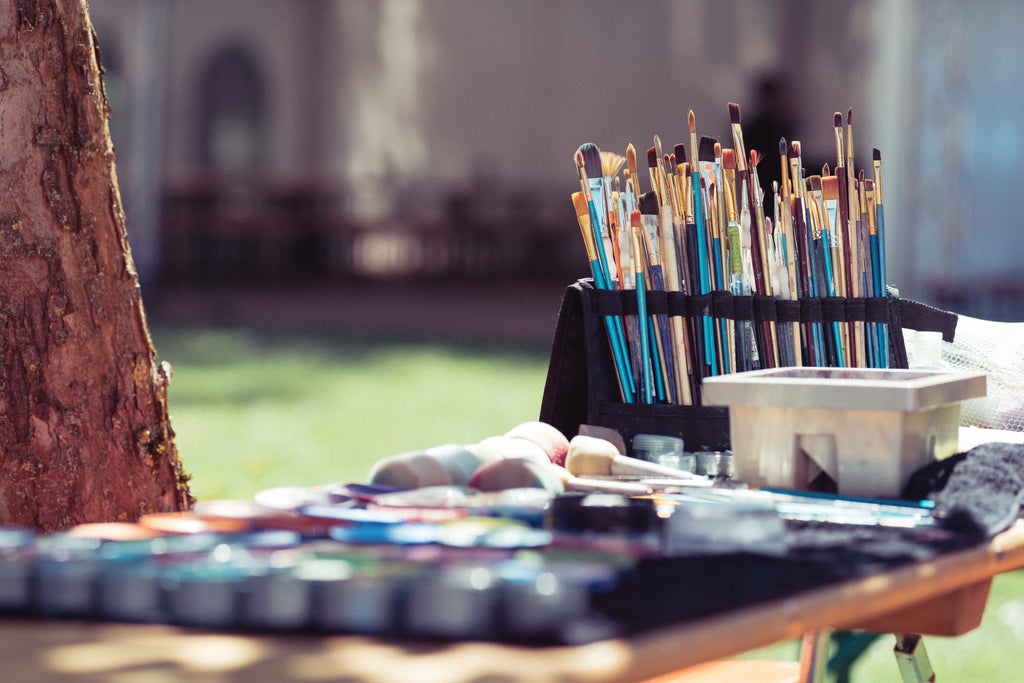 close up of painting supplies on a desk outside