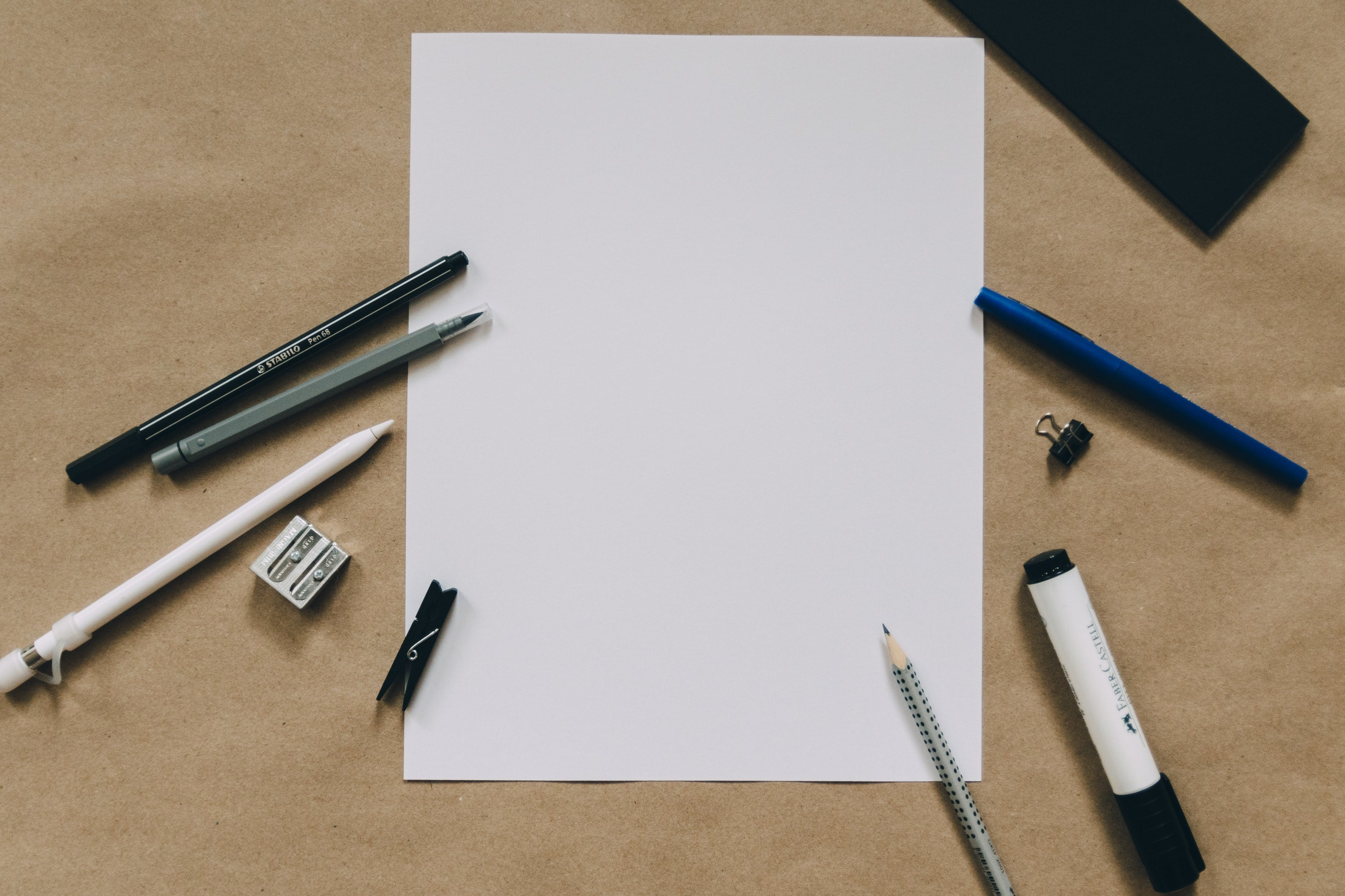 Birds Eye View of blank piece of paper with various types of pens around it - photo by Kelly Sikkema