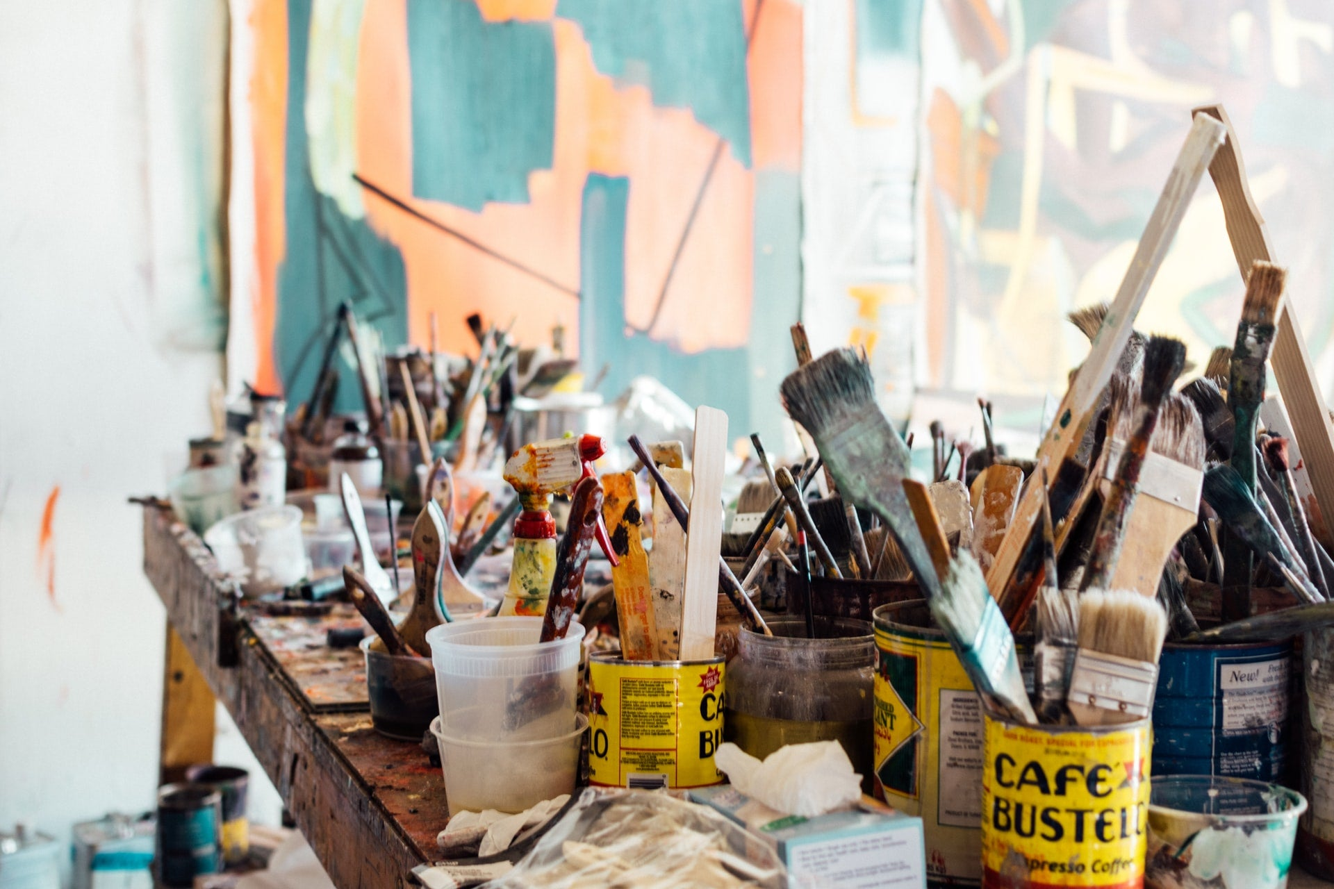 Image of messy artist studio with cans of paintbrushes filling the table
