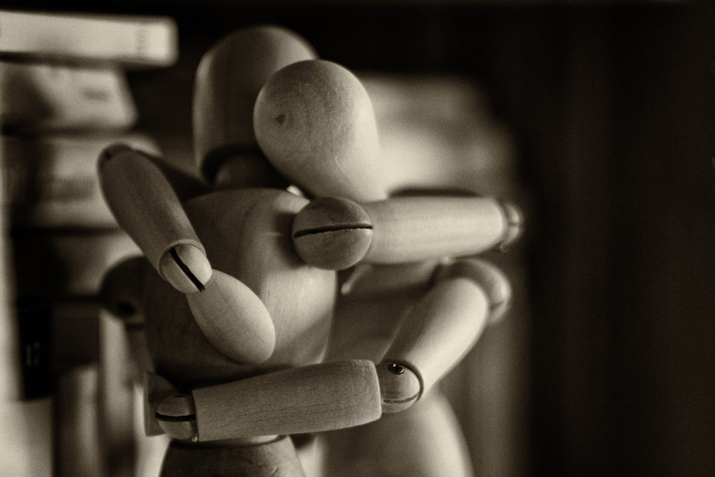 Two drawing figurines hugging each other in a black and white photo