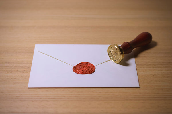 Image of a white envelope with a red wax seal and stamp off to the side