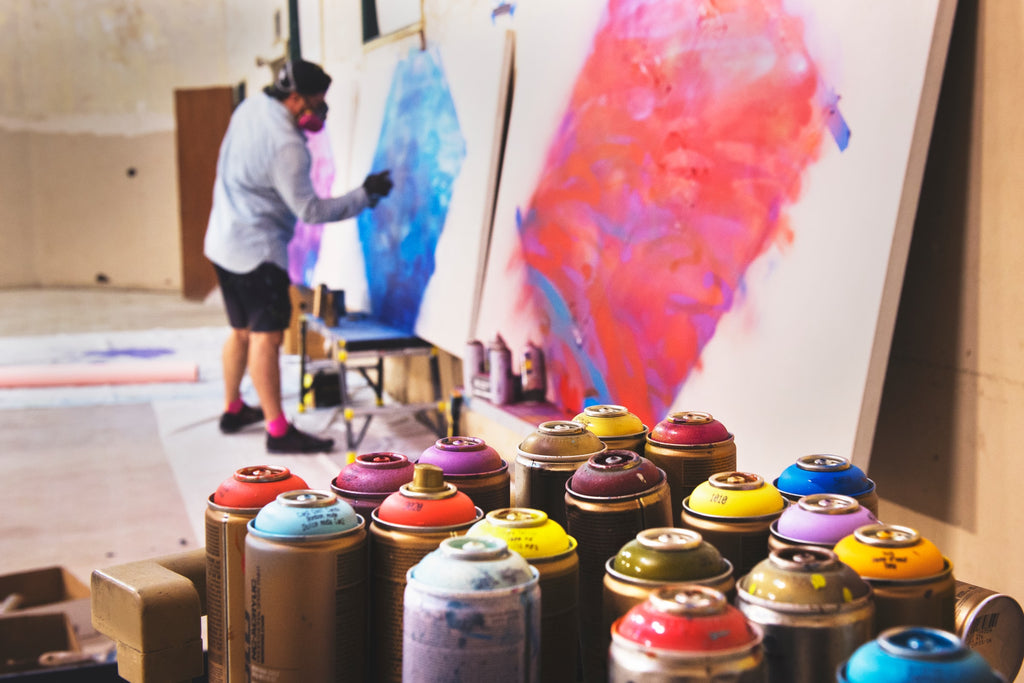 Tim Mossholder photograph, close up of paint spray cans while in the distance and artists works on large canvases