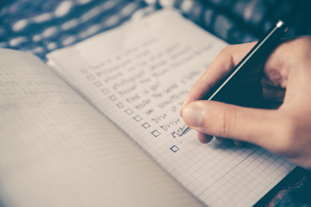close up of person writing a to do list in a journal