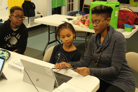 Netia showing a young STEM after-school program participant how to design a Black Panther inspired Kimoyo Bead using CAD (Computer Aided Design). [October 2018]
