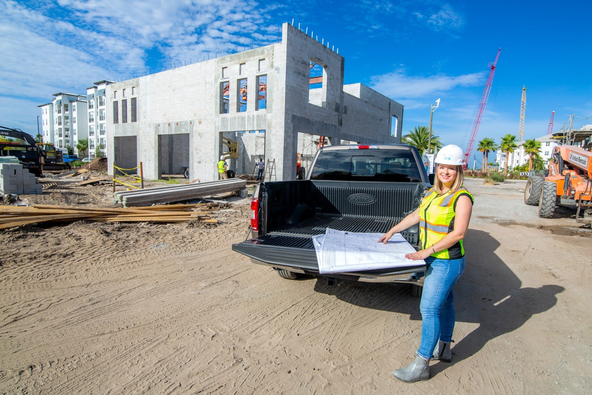 Britney Mroczkowski looking at building plans on a job site with BTI Partners