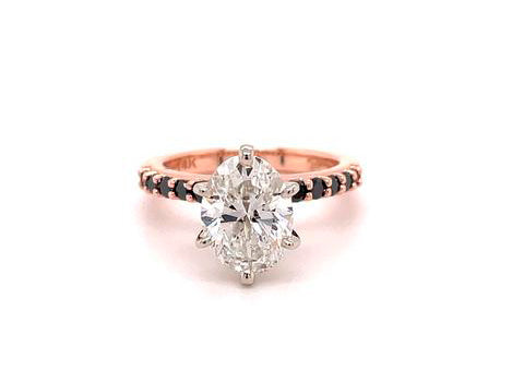 Alternative engagement ring in rose gold with black diamonds on the band.
