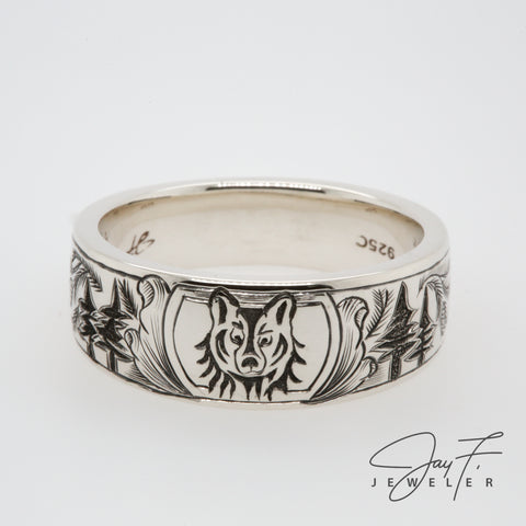 Photo of a hand engraved wolf and trees on a platinum custom ring.