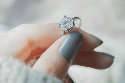 Image of woman's hand holding a diamond solitaire ring.