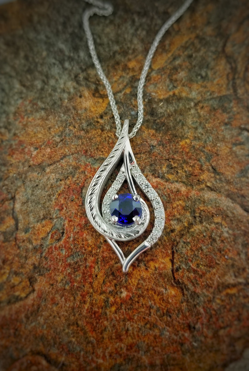 hand engraved Autism pendant featuring a center blue sapphire and diamonds