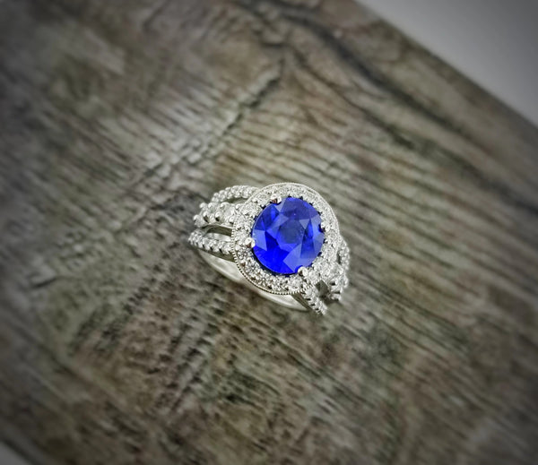 White gold split shank ring featuring a 3.26ct oval blue Sapphire and 1.26ctw of ideal cut diamond melee