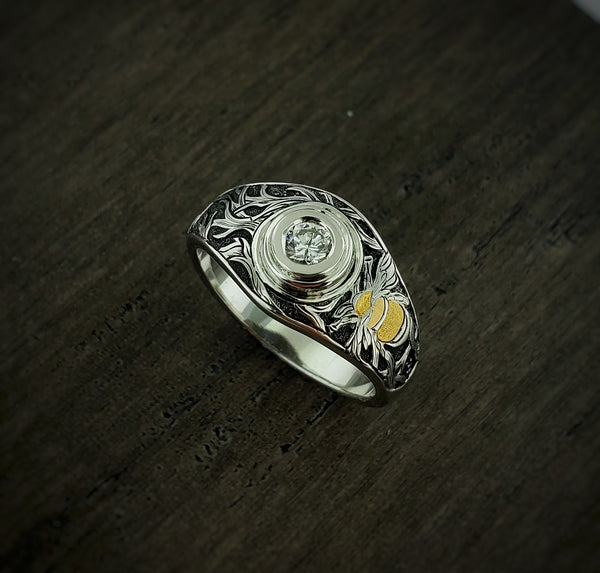 Hand engraved bee ring with round center diamond set in a bezel