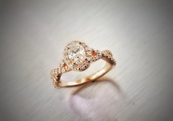 Rose gold criss-cross band diamond engagement ring featuring a .606ct oval diamond center