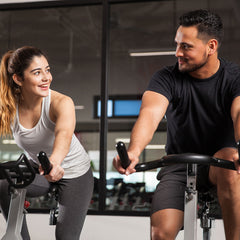 A man and woman exercise at a gym.