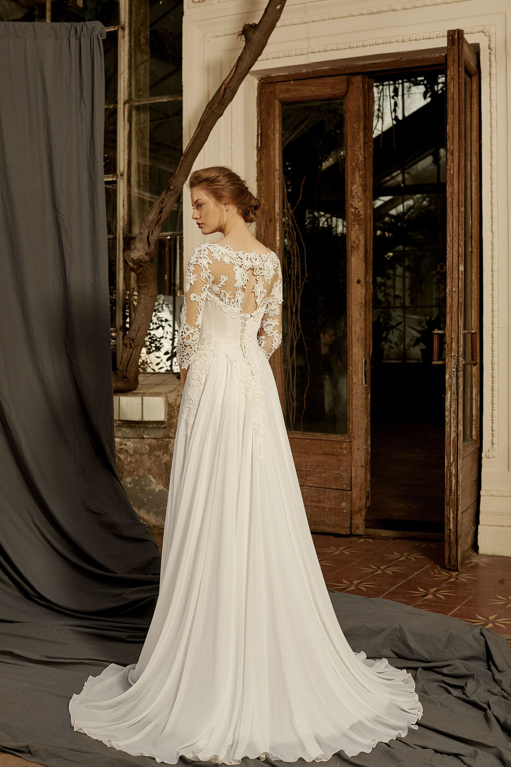 This elegant sheath gown has a sweetheart neckline and long sleeves decorated with intricate lace.