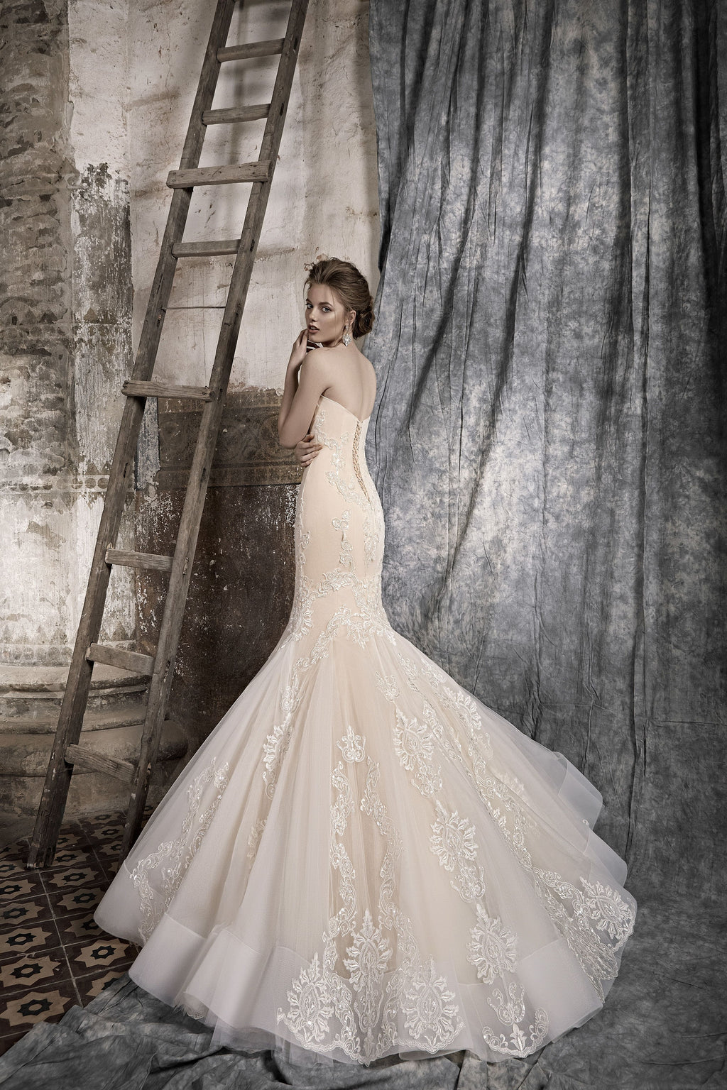 This figure-flattering mermaid wedding gown features a beautiful sweetheart neckline. Its fitted bodice adorned with lace and sparkling sequins.