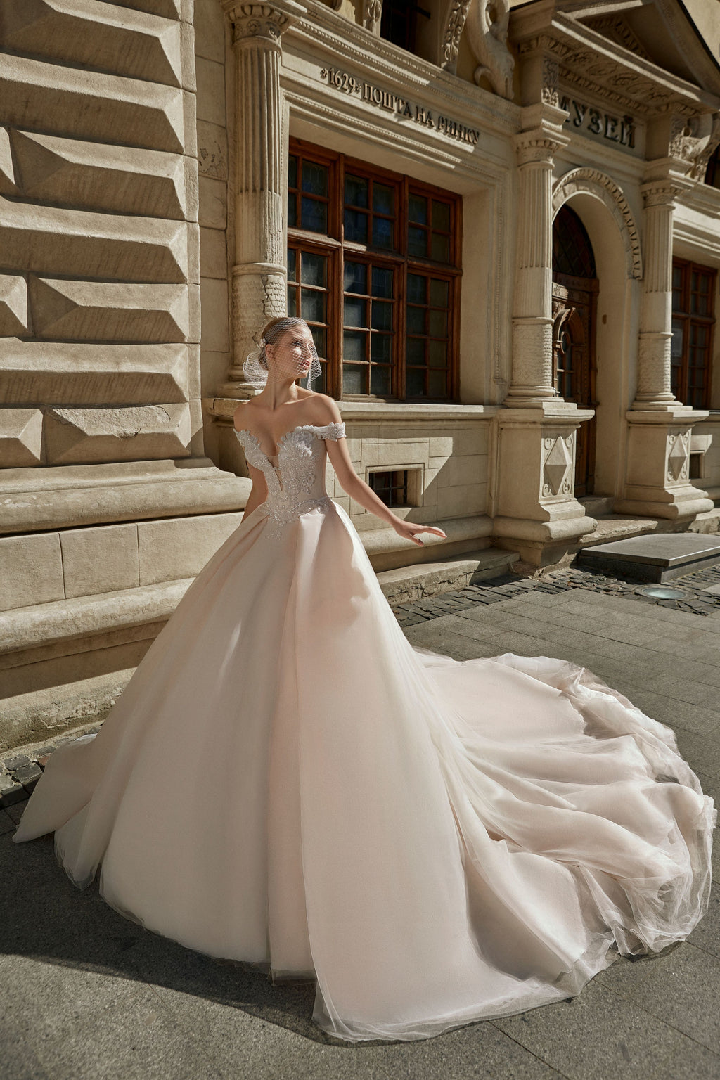 This princess ball gown has a sweetheart bodice decorated with hand-embroidered beaded lace, off-shoulder straps and a tulle and organza layered skirt complete with a wide train.