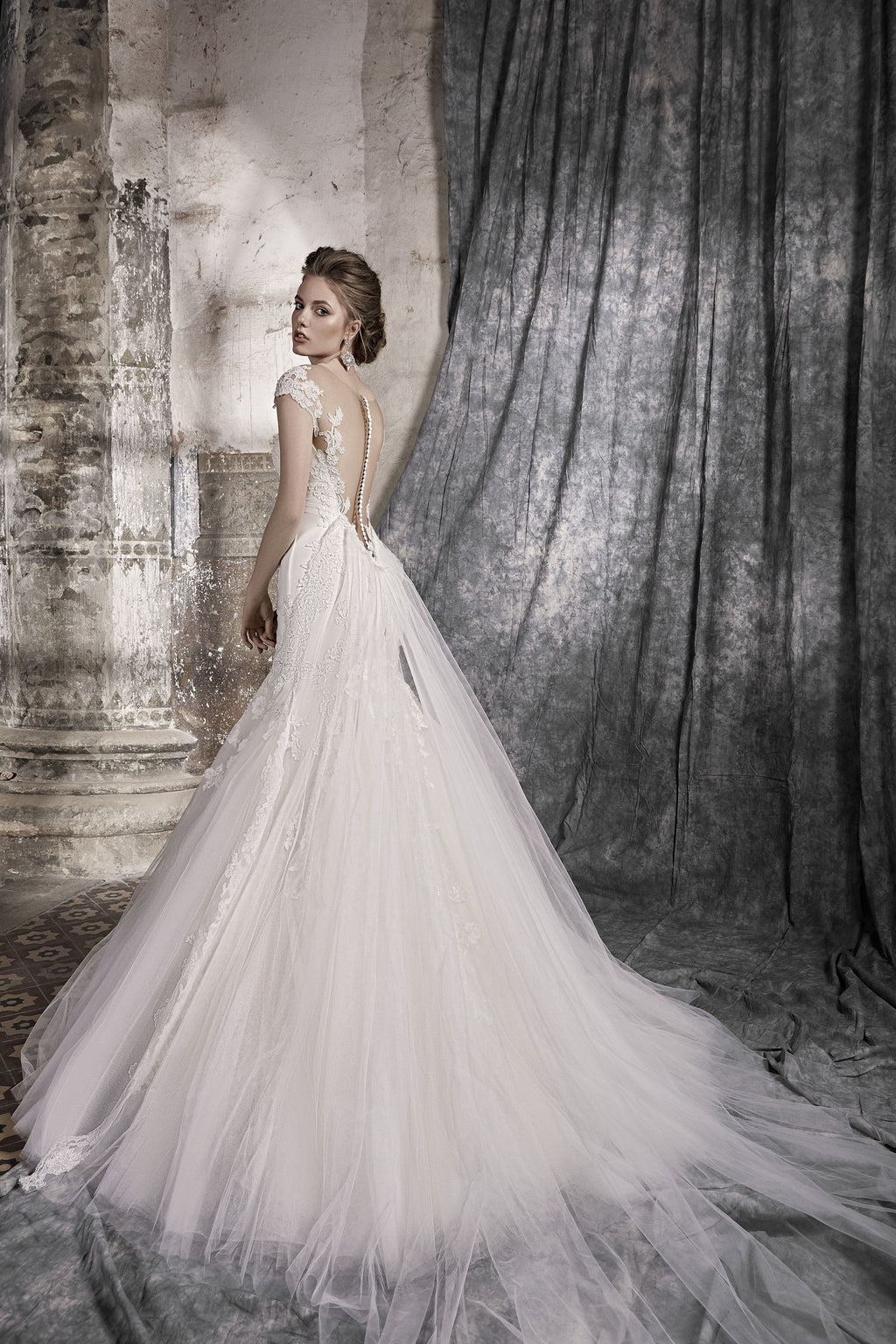 This gorgeous mermaid dress with lace appliques features a sweetheart bodice draped with tulle, an illusion V-back with a line of buttons, and a removable tulle train.